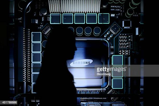A woman walks past the Samsung Electronics Co logo displayed at the Semiconductor Rider experience at the company's d'light showroom in Seoul South...