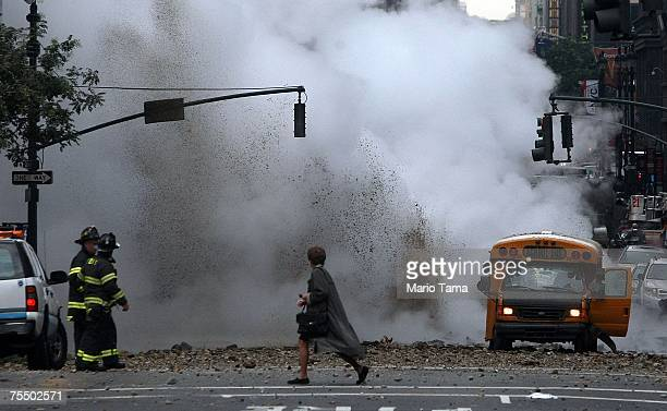A woman walks past the scene of a steam pipe explosion on Lexington Avenue July 18 2007 in New York City Steam and mud were forced from the ground...