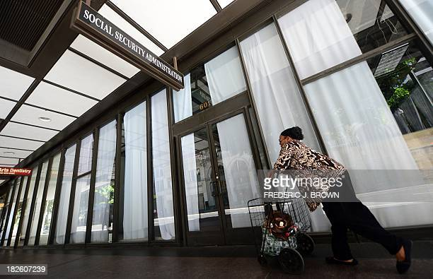 Woman walks past the Social Security Administration office in downtown Los Angeles, on October 1, 2013 in California. US monuments closed, offices...
