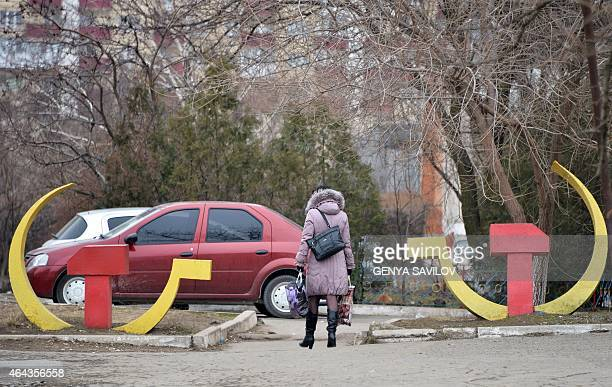 A woman walks past the Soviet symbols of the hammer and sickle in the southeastern Ukrainian city of Mariupol Donetsk region on February 25 2015...