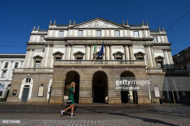 A woman walks past the Teatro alla Scala in the northern Italian city of Milan on August 20 2017 / AFP PHOTO / MIGUEL MEDINA