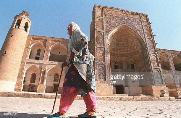 A woman walks past the UluhBeg Madrassah a Koranic school in the Uzbek town of Bukhara on the old Silk Road trade route 08 August The Madrassah...