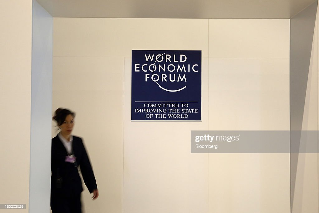 A woman walks past the World Economic Forum logo displayed at the Dalian International Conference Center in Dalian, China, on Tuesday, Sept. 10, 2013. The World Economic Forum Annual Meeting Of The New Champions 2013 will be held in Dalian from Sept. 11 to 13. Photographer: Tomohiro Ohsumi/Bloomberg via Getty Images