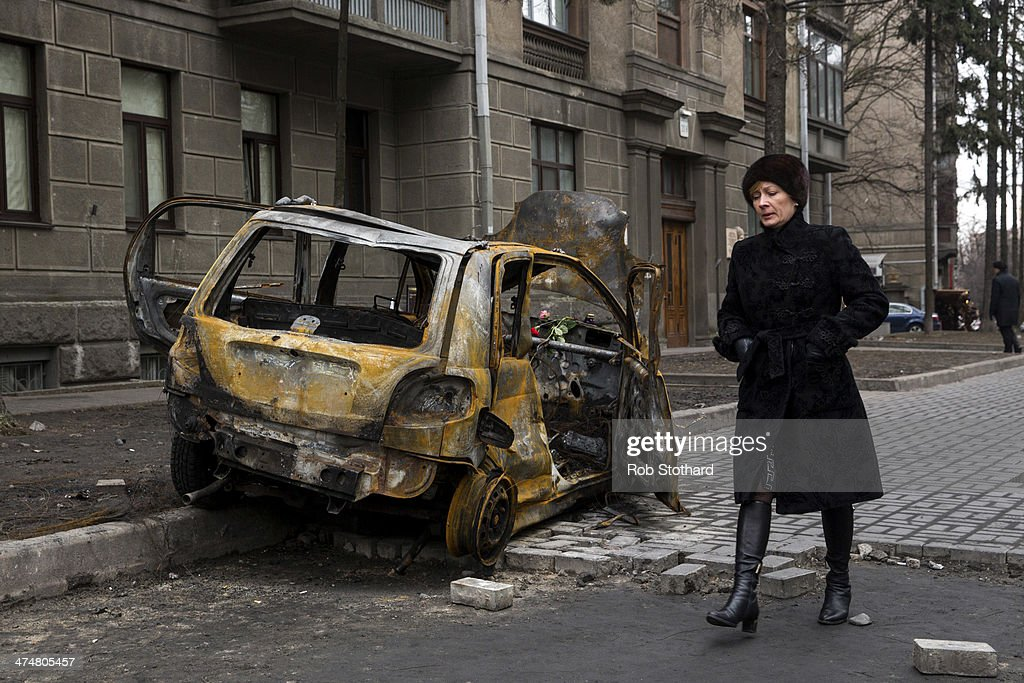 A woman walks past the wreckage of a car close to the Ukrainian Parliament building on February 25, 2014 in Kiev, Ukraine. Ukraine's interim President Olexander Turchynov is due to form a unity government, as UK and US foreign ministers meet to discuss emergency financial assistance for the country.