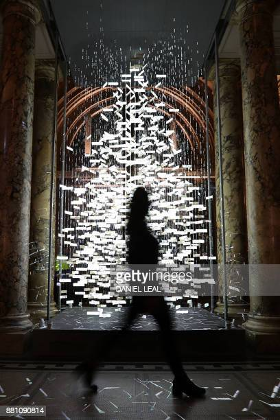 A woman walks past this year's Christmas Tree The Singing Tree designed by stage and performance designer Es Devlin in the grand entrance of the...