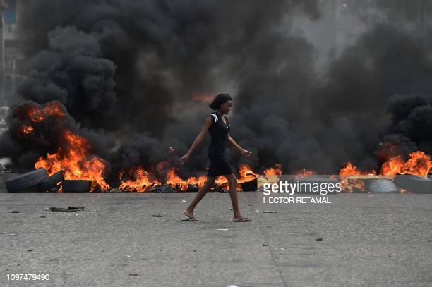 Woman walks past tire barricades set ablaze by demonstrators on the fourth day of protests in Port-au-Prince, February 10 against Haitian President...