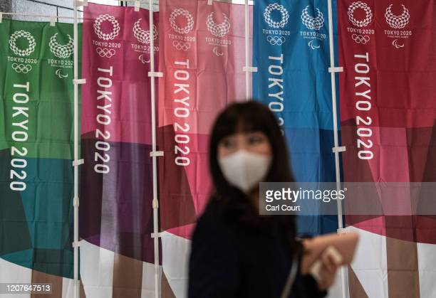 Woman walks past Tokyo 2020 Olympics banners on March 19, 2020 in Tokyo, Japan. As Japanese and IOC officials continued to insist that the Games...
