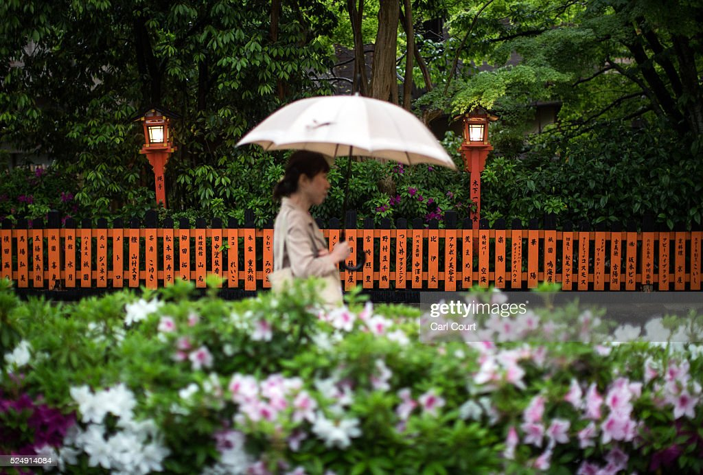 A woman walks past traditional lamps and a fence bearing written messages on April 27, 2016 in Kyoto, Japan. Now the seventh largest city in Japan, Kyoto was once the Imperial capital for more than one thousand years, it is now the capital city of Kyoto Prefecture and a major part of the Kyoto-Osaka-Kobe metropolitan area.