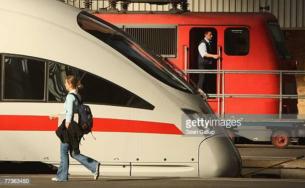 A woman walks past trains of German state railways Deutsche Bahn as an enginner stands in the doorway of his locomotive at Hauptbahnhof train station...