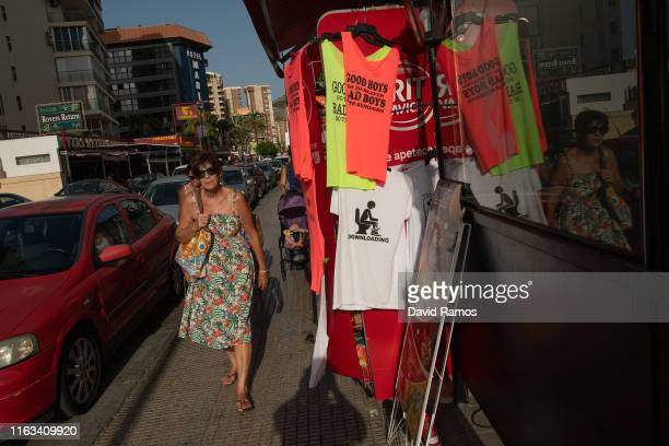 A woman walks past tshirts for tourists on July 21 2019 in Benidorm Spain More than 39 million of tourists are expected to visit Spain by the end of...