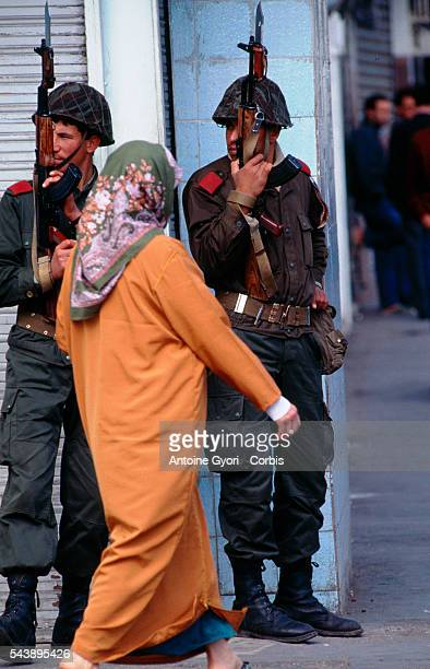 A woman walks past two army soldiers with the Algerian armed forces patrolling the streets of Algiers during the political crises which stemmed from...
