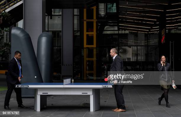 A woman walks past two men playing table tennis outside the Leadenhall Building as the deadline nears for companies to report their gender pay gap on...