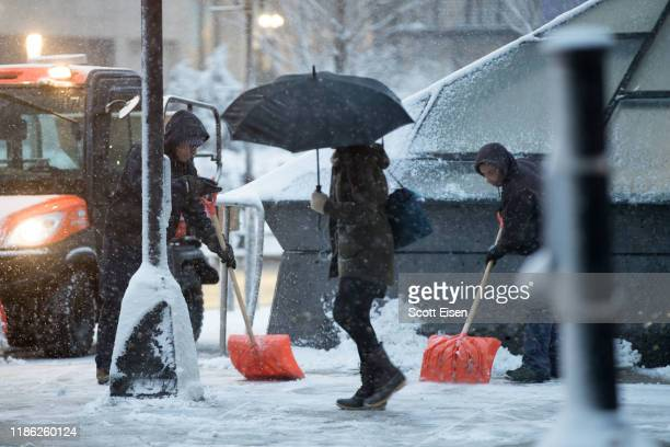 A woman walks past two workers clearing snow from a sidewalk near South Station as the first winter storm of the season impacts the region on...