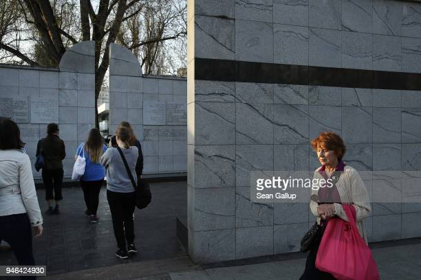 A woman walks past visitors at a memorial to the Umschlagplatz the spot where Jews in the former Warsaw Ghetto had to gather before deportation to...