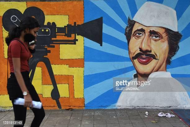 Woman walks past wall mural depicting Bollywood actor Nilu Phule, in Mumbai on March 4, 2021.