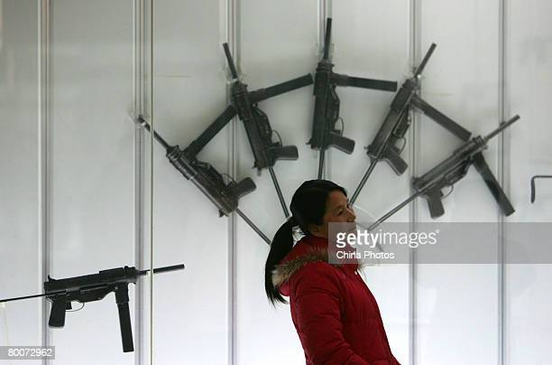 A woman walks past weapons at the Military Museum of Chinese People's Revolution on March 1 2008 in Beijing China From March 1 the Military Museum of...
