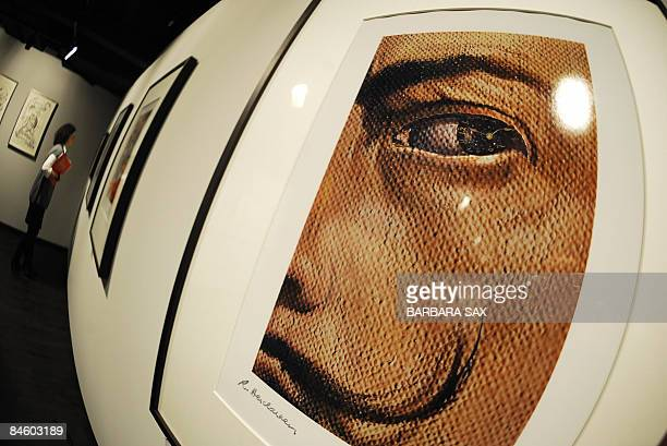 A woman walks past works by Spanish artist Salvador Dali as in the foreground can be seen a photocollage titled 'Macrophotographic SelfPortrait with...