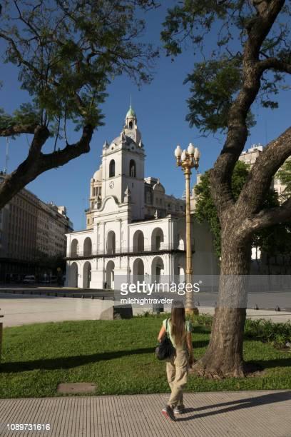 Woman walks Plaza de Mayo park Cabildo Buenos Aires Argentina