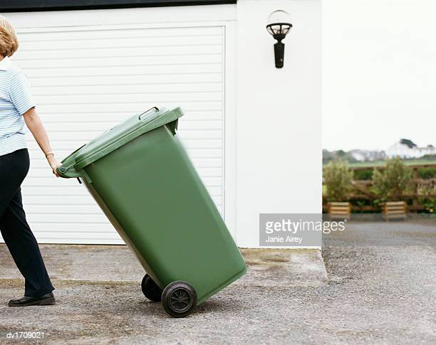 woman walks pulling a bin - garbage bin stock pictures, royalty-free photos & images
