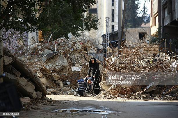 A woman walks pushing a pram between the rubble of destroyed buildings in the besieged rebel bastion of Douma on December 13 2014 Douma a rebel...