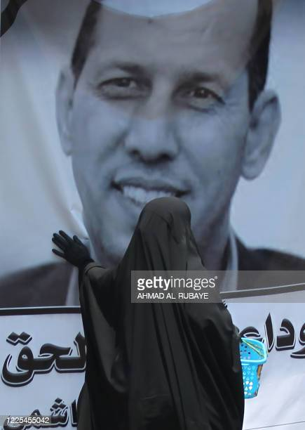 Woman walks reaches to touch the poster of slain Iraqi jihadism expert Hisham al-Hashemi, who was shot outside his house two days prior, in the...