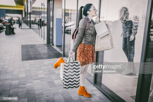 woman walks shopping center - state of emergency stock pictures, royalty-free photos & images