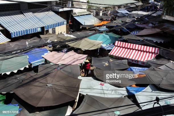 A woman walks though a market is covered by parasols in Ho Chi Minh City Vietnam on Wednesday June 20 2018 For decades Vietnamese have shopped...