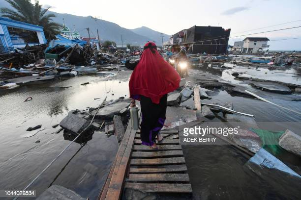 TOPSHOT A woman walks through a devastated area in Palu Indonesia's Central Sulawesi on October 1 after an earthquake and tsunami hit the area on...