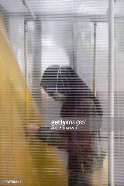 A woman walks through a disinfectant chamber as a preventive measure against the COVID19 coronavirus before entering a shopping mall in Surabaya on...