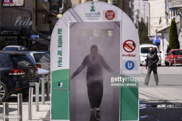 Woman walks through a disinfection chamber set up as a preventive measure amid concerns over the spread of the COVID-19 in front of a hospital in...