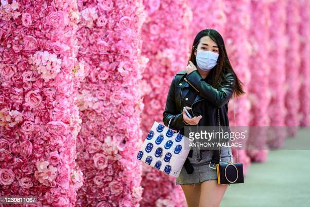 Woman walks through a floral themed passageway in Hong Kong on January 27, 2021.