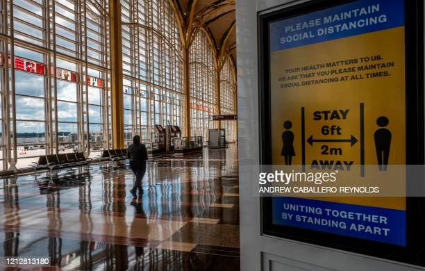 A woman walks through a mostly empty Ronald Reagan Washington National Airport in Arlington Virginia on May 12 2020 The airline industry has been hit...