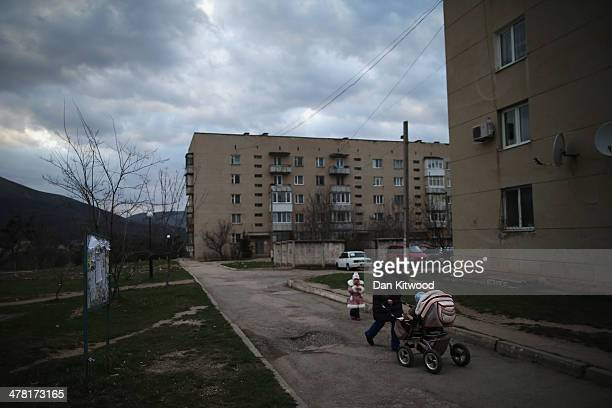 A woman walks through a residential estate next to the perimeter of a Ukrainian military base on March 12 2014 in Simferopol Ukraine As the standoff...