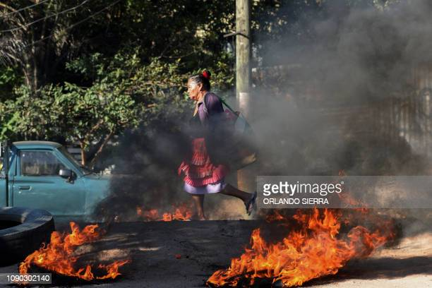 A woman walks through a roadblock mounted by supporters of the LIBRE opposition party in the workingclass neighborhood of El Carrizal during protests...