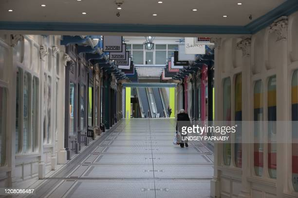 A woman walks through a shopping arcade with the shops closed due to coronavirus in Leeds northern England on March 24 2020 after Britain ordered a...