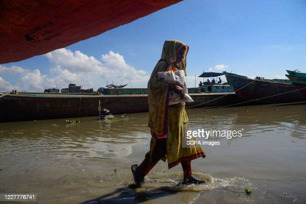 Woman walks through a submerged road. The flood situation is worsening in Munshiganj. Due to the heavy rain, the water level of the Padma River has...