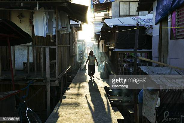 A woman walks through an alleyway in the Isla Verde shantytown of Davao Mindanao the Philippines on Friday Dec 11 2015 Davao city's reputation as one...