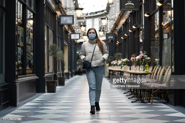 A woman walks through an empty Castle Arcade wearing a surgical mask on March 17 2020 in Cardiff Wales Boris Johnson held the first of his public...
