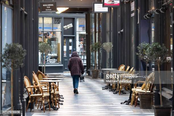 A woman walks through an empty Duke Street Arcade home to many small businesses on March 17 2020 in Cardiff Wales Boris Johnson held the first of his...