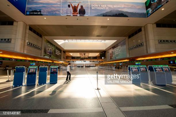 A woman walks through an empty Tom Bradley Terminal at Los Angeles International Airport during the outbreak of the novel coronavirus which causes...