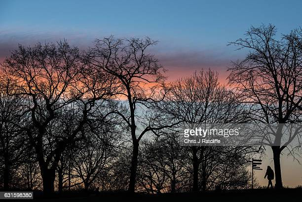 A woman walks through Brockwell Park as the sun rises on January 13 2017 in London United Kingdom The Met Office has issued a yellow 'be aware'...