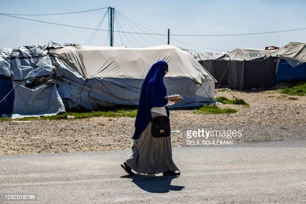 Woman walks through Camp Roj, where relatives of people suspected of belonging to the Islamic State group are held, in the countryside near...