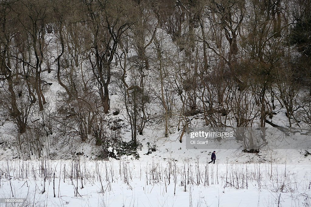 A woman walks through deep snow in Dovedale in the Peak District on January 26, 2013 in Stanshope, England.