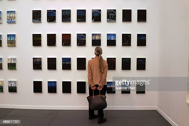 A woman walks through exhibits at the New York Frieze Art Fair on May 9 2014 in New York City Held on Randalls Island a short water taxi car or bus...