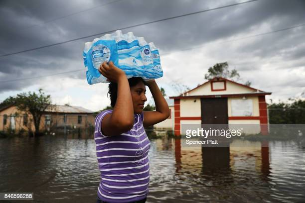 A woman walks through flooded streets in the rural migrant worker town of Immokalee which was especially hard hit by Hurricane Irma on September 13...