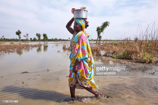 Woman walks through floodwaters in Yusuf Batir refugee camp in Maban, South Sudan on November 25, 2019. - Large areas of eastern South Sudan have...