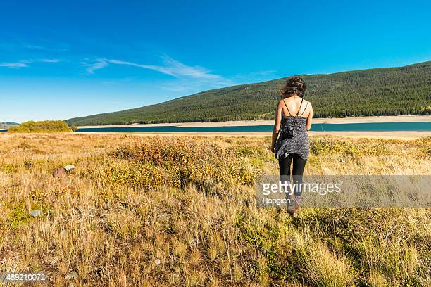 Woman Walks Through Grassy Lake Landscape in Glacier National Park