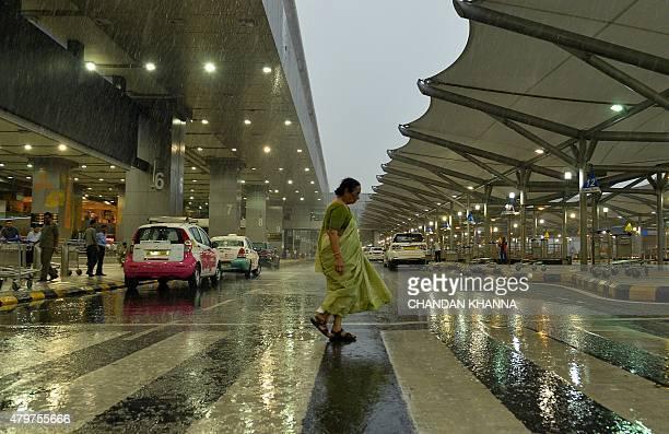 A woman walks through heavy monsoon rainstorm at Indira Gandhi International Airport in New Delhi on July 7 2015 PHOTO / CHANDAN KHANNA