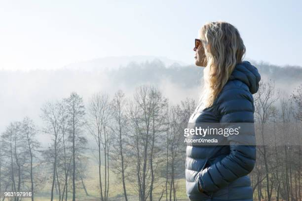 woman walks through hilly meadow in mist - padded jacket stock pictures, royalty-free photos & images