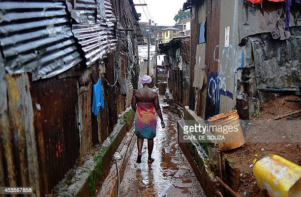 A woman walks through Kroo town slum in Freetown on August 13 2014 The World Health Organisation revealed that the latest death toll from the Ebola...